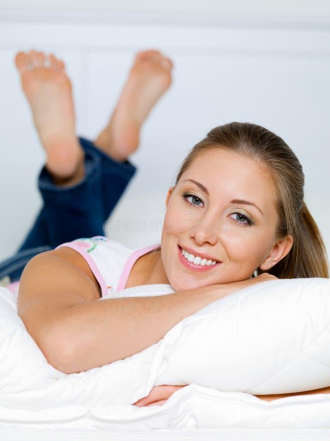 Το πορτρέτο της ευτυχούς γυναίκας βρίσκεται σε ένα μαξιλάρι στοκ εικόνες
