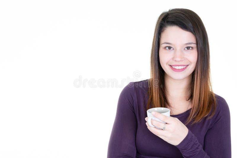 Το πορτρέτο της ευτυχούς νέας γυναίκας με το φλιτζάνι του καφέ αντιγράφει κατά μέρος το διάστημα στοκ φωτογραφία