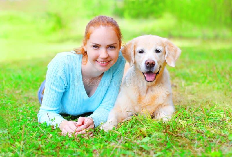 Το πορτρέτο της ευτυχούς χαμογελώντας γυναίκας ιδιοκτητών και του χρυσού Retriever σκυλιού βρίσκεται στο καλοκαίρι χλόης στοκ εικόνες