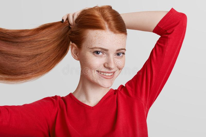 Το πορτρέτο της ευτυχούς redhead αρκετά νέας γυναίκας καταδεικνύει πολυτελή μακρυμάλλη της, κάνει την ουρά πόνι, που πηγαίνει να  στοκ φωτογραφίες με δικαίωμα ελεύθερης χρήσης