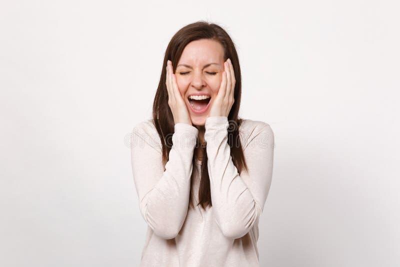 Το πορτρέτο της εύθυμης νέας γυναίκας στα ελαφριά ενδύματα που κρατούν τα μάτια έκλεισε, βάζοντας τα χέρια στα μάγουλα που απομον στοκ φωτογραφία