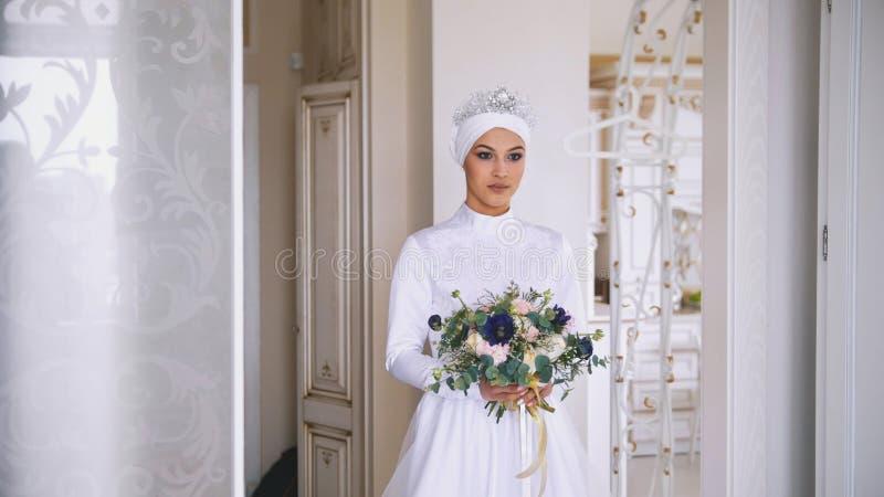 Το πορτρέτο της νέας μουσουλμανικής νύφης με τον επαγγελματία αποτελεί στο άσπρο φόρεμα με τα λουλούδια στοκ εικόνες