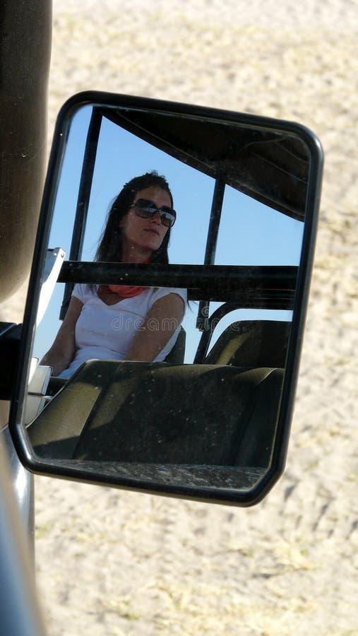 Το πορτρέτο της νέας όμορφης γυναίκας απεικόνισε στον καθρέφτη αυτοκινήτων ` s ενός τζιπ σαφάρι κατά τη διάρκεια ενός παιχνιδιού  στοκ εικόνα με δικαίωμα ελεύθερης χρήσης
