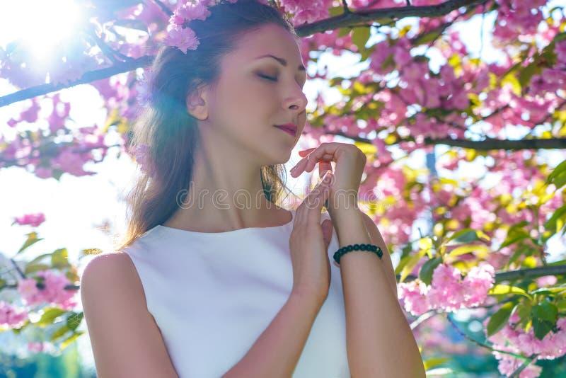 Το πορτρέτο της νέας όμορφης γυναίκας με τα ρόδινα λουλούδια στην τρίχα της είναι στο άσπρο φόρεμα θέτει την προσφορά στο δέντρο  στοκ φωτογραφίες με δικαίωμα ελεύθερης χρήσης