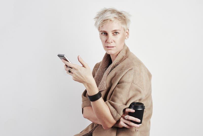 Το πορτρέτο της ξανθής καυκάσιασης ανήσυχης συγκίνησης γυναικών πίνει το take-$l*away καφέ, χρησιμοποιώντας το smartphone στο άσπ στοκ εικόνες