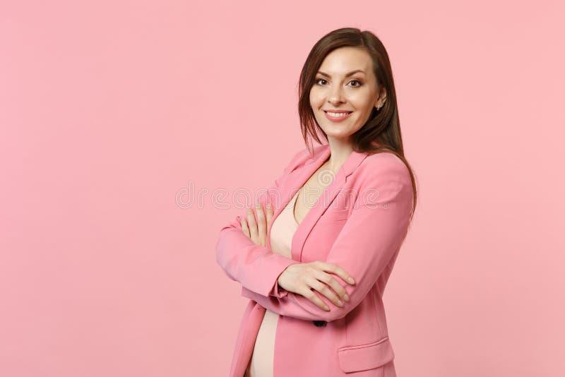Το πορτρέτο της χαμογελώντας ζαλίζοντας νέας γυναίκας στο σακάκι που στέκεται, που κρατά τα χέρια διέσχισε απομονωμένος στην κρητ στοκ εικόνες