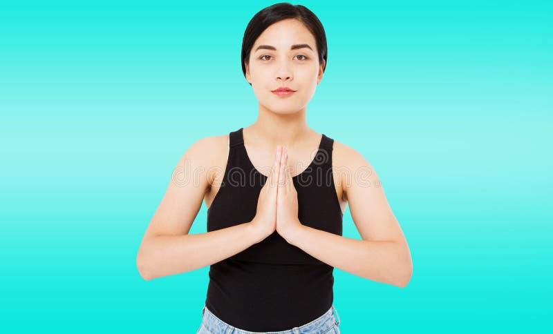 Το πορτρέτο της χαριτωμένης επιτυχούς ασιατικής, κορεατικής γυναίκας παρουσιάζει namaste χειρονομία στο μπλε υπόβαθρο, διάστημα α στοκ εικόνες