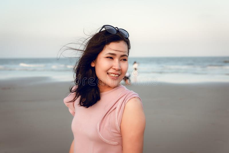 Το πορτρέτο της όμορφης γυναίκας απολαμβάνει και χαλαρώνει στην παραλία στο χρόνο διακοπών, ασιατική συγκίνηση ευτυχίας κοριτσιών στοκ εικόνα