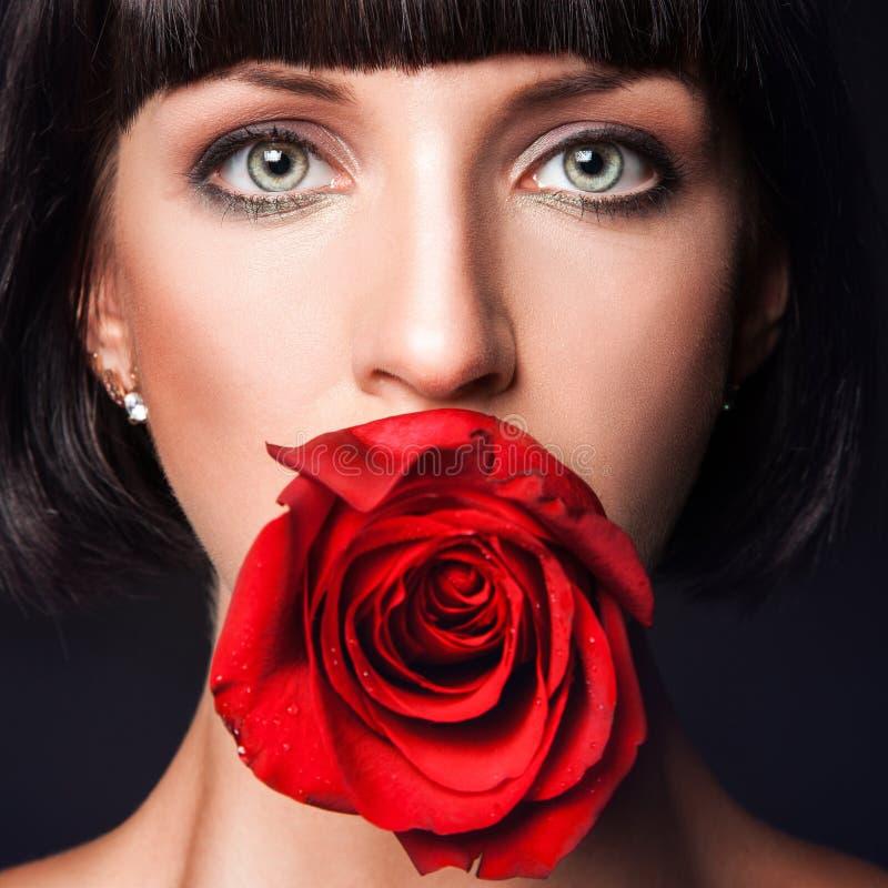 Το πορτρέτο της όμορφης γυναίκας με το κόκκινο αυξήθηκε στο στόμα στοκ φωτογραφία