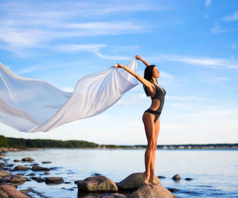 Το πορτρέτο της όμορφης γυναίκας στο μπικίνι με το άσπρο μαντίλι είναι στοκ εικόνες