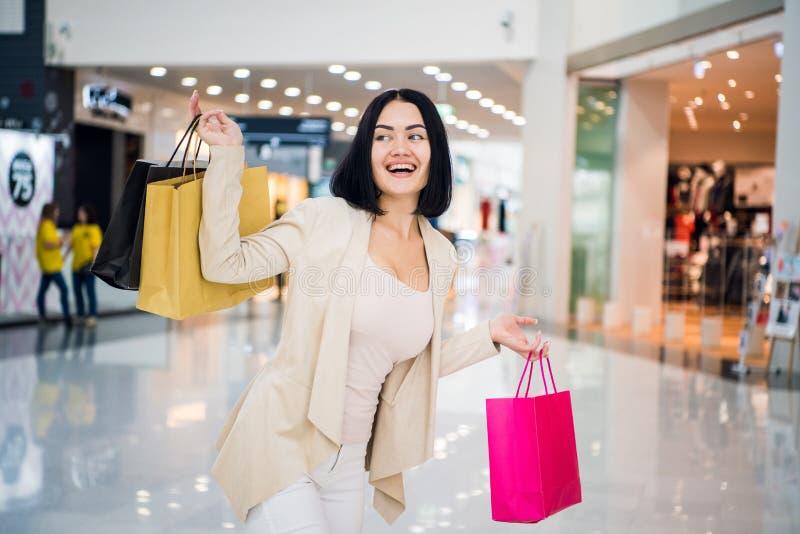 Το πορτρέτο της όμορφης νέας γυναίκας με τις αγορές τοποθετεί την έξοδο σε ένα ξεφάντωμα αγορών σε σάκκο στοκ φωτογραφίες