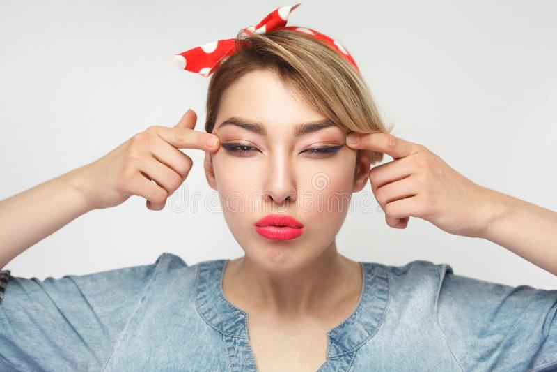 Το πορτρέτο της όμορφης νέας γυναίκας τύφλωσης στο περιστασιακό μπλε πουκάμισο τζιν με το makeup και κόκκινο headband που στέκοντ στοκ φωτογραφίες