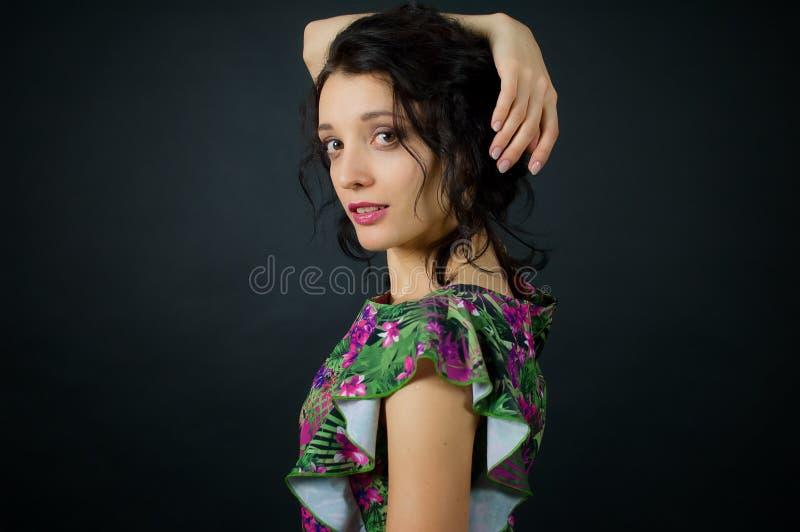 Το πορτρέτο της beautuful νέας γυναίκας με το makeup και ένα μοντέρνο hairstyle θέτει στο στούντιο στη μαύρη φθορά υποβάθρου στοκ φωτογραφίες