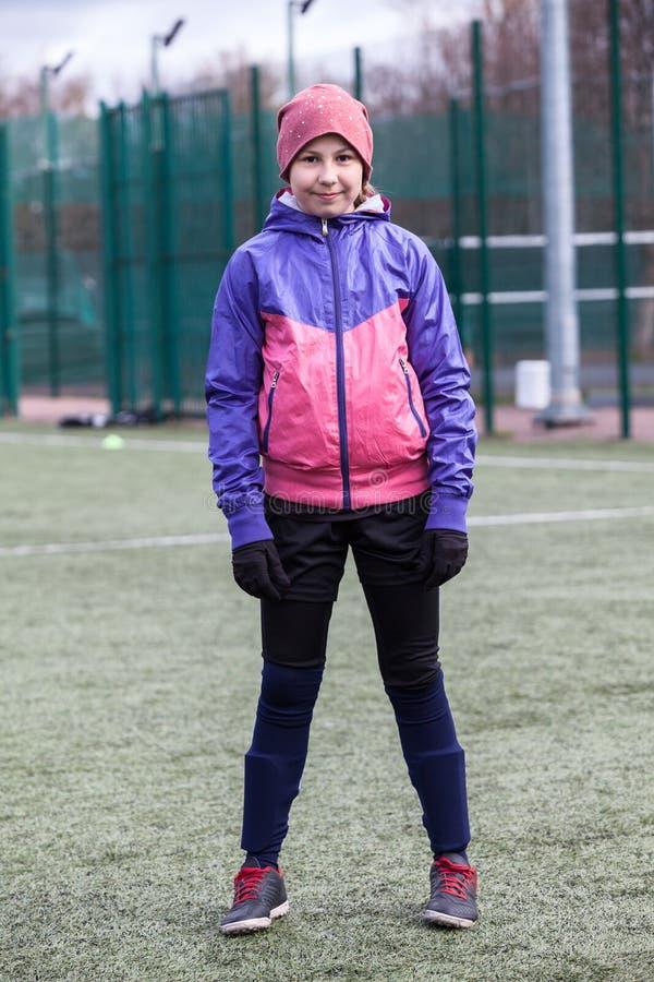 Το πορτρέτο της eleven-year στάσης ποδοσφαιριστών κοριτσιών στον τομέα χλόης σε ομοιόμορφο και οι μπότες στοκ φωτογραφίες