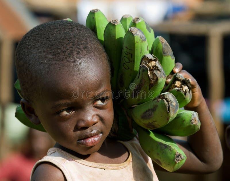 Το πορτρέτο του αγοριού με μια σύνδεση των μπανανών που πηγαίνει στην αγορά αυτοί που πωλούν στοκ εικόνες