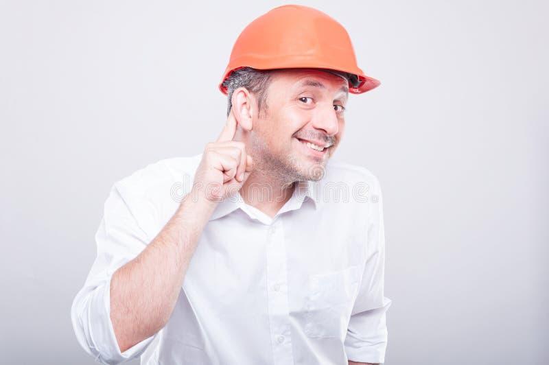 Το πορτρέτο του αναδόχου που φορά hardhat την παραγωγή μπορεί ` τ να ακούσει τη χειρονομία στοκ φωτογραφία