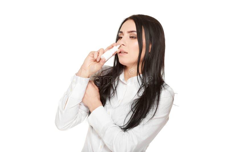 Το πορτρέτο του ανθυγειινού κοριτσιού πνίγει τα σταγονίδια στη μύτη από το μπουκάλι στοκ φωτογραφία
