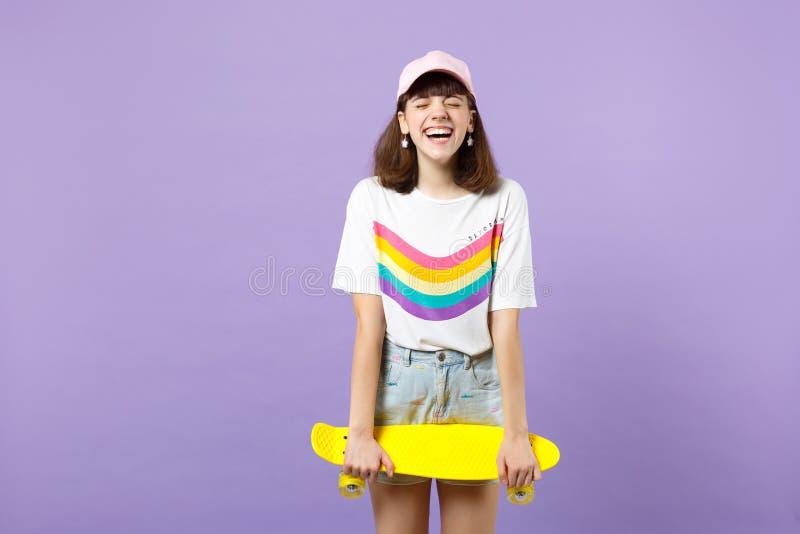 Το πορτρέτο του γελώντας κοριτσιού εφήβων στα ζωηρά ενδύματα που κρατούν τα μάτια έκλεισε κίτρινο skateboard εκμετάλλευσης που απ στοκ φωτογραφία με δικαίωμα ελεύθερης χρήσης