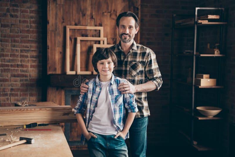 Το πορτρέτο του γοητευτικού θαυμάσιου αγκαλιάσματος παιδιών παιδιών μπαμπάδων αγκαλιάζει τους γενειοφόρους βιοτέχνες γκαράζ ώμων  στοκ φωτογραφία με δικαίωμα ελεύθερης χρήσης