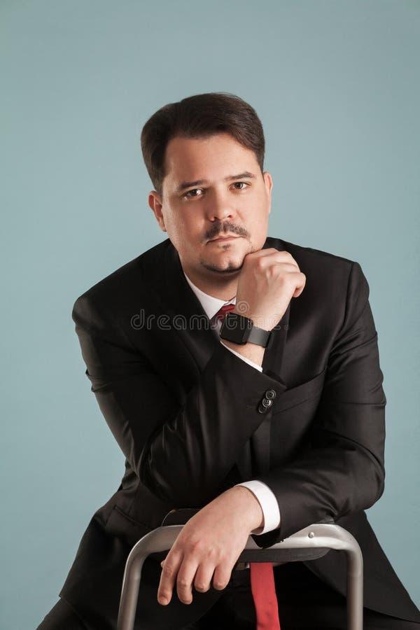 Το πορτρέτο του ενεργούντος επιχειρηματία συνεδρίασης βλαστών σχετικά με το πηγούνι, κοιτάζει στοκ εικόνες
