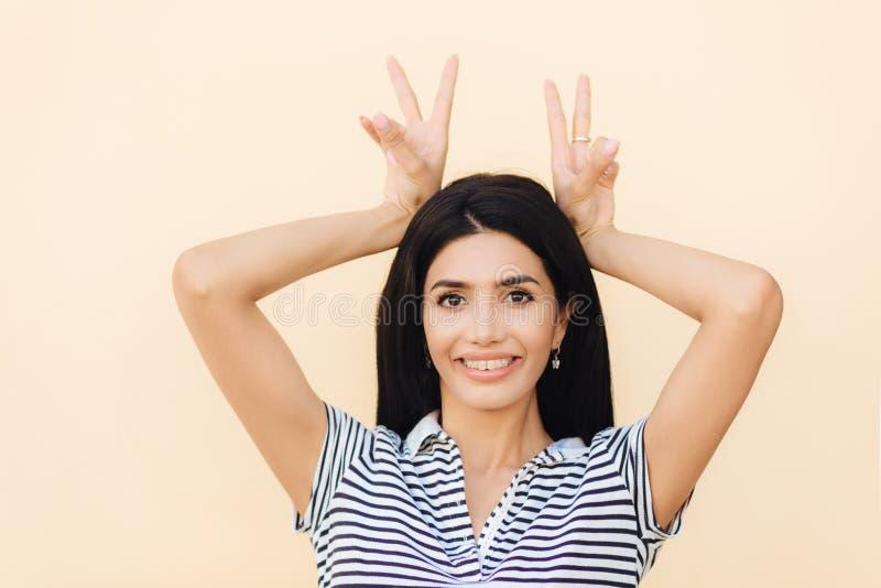 Το πορτρέτο του ευτυχούς θηλυκού brunette κάνει τη χειρονομία κέρατων, έχει τη διασκέδαση και foolishes με τους φίλους, η ύπαρξη  στοκ εικόνες