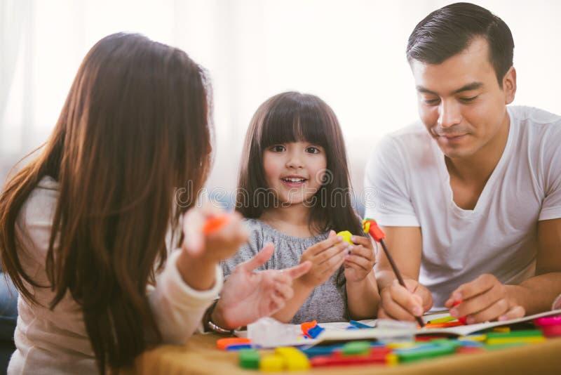 Το πορτρέτο του ευτυχούς κοριτσιού οικογενειακών κορών μαθαίνει να χρησιμοποιεί το ζωηρόχρωμο παιχνίδι φραγμών ζύμης παιχνιδιού μ στοκ εικόνες