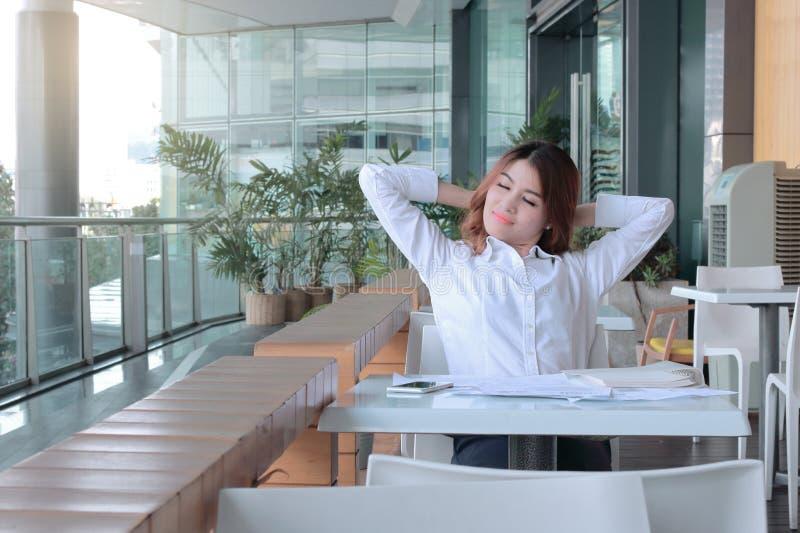 Το πορτρέτο του ευτυχούς νέου ασιατικού συναισθήματος επιχειρησιακών γυναικών χαλαρώνει και αγαθό στο γραφείο της στοκ φωτογραφίες με δικαίωμα ελεύθερης χρήσης