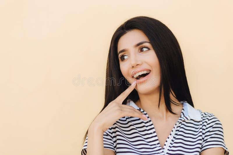 Το πορτρέτο του ευτυχούς νέου θηλυκού με το σκοτάδι που η μακριά ευθεία τρίχα, έχει το ευρύ χαμόγελο, δείχνει στο στόμα της, κατα στοκ εικόνα