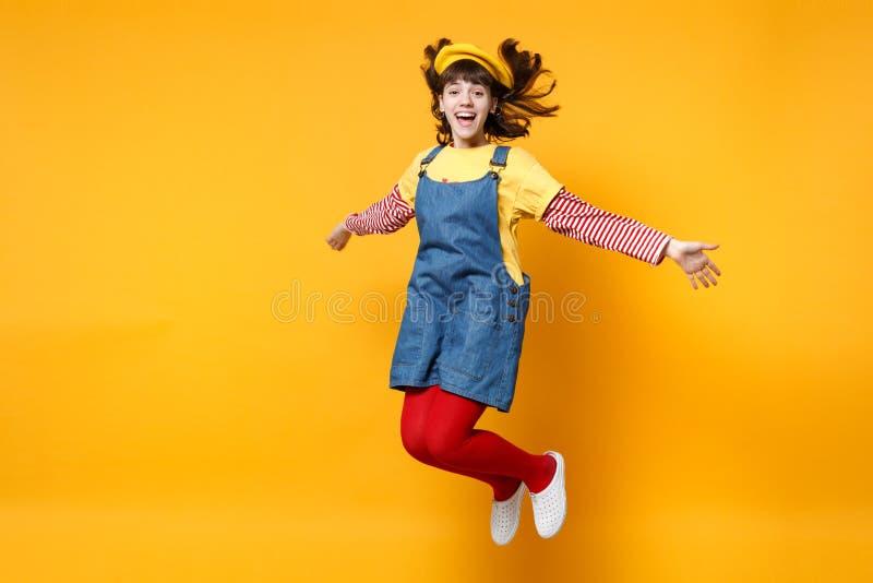 Το πορτρέτο του εύθυμου εφήβου κοριτσιών γαλλικά beret και το τζιν sundress που πηδούν με την κυματίζοντας τρίχα απομόνωσε σε κίτ στοκ φωτογραφίες