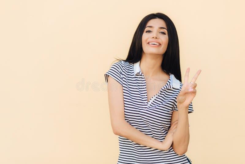 Το πορτρέτο του εύθυμου θηλυκού brunette παρουσιάζει χειρονομία ειρήνης, κρατά δύο δάχτυλα αυξημένα, ντύνει το ευχάριστο χαμόγελο στοκ εικόνες
