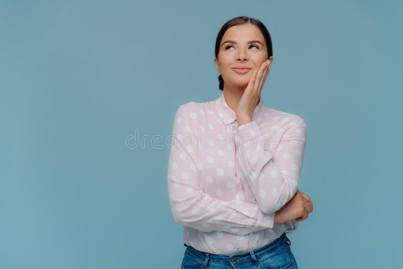 Το πορτρέτο του εύθυμου ικανοποιημένου θηλυκού brunette αγγίζει το μάγουλο ήπια, κοιτάζει ανωτέρω, ονειρεύεται για κάτι ευχάριστο στοκ φωτογραφία με δικαίωμα ελεύθερης χρήσης