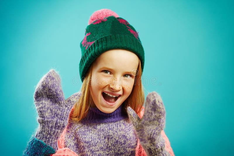 Το πορτρέτο του εύθυμου κοριτσιού παιδιών φορά τα χειμερινά γάντια, το θερμό πουλόβερ, το καπέλο με το pompom και το δικτυωτό μαν στοκ εικόνα με δικαίωμα ελεύθερης χρήσης