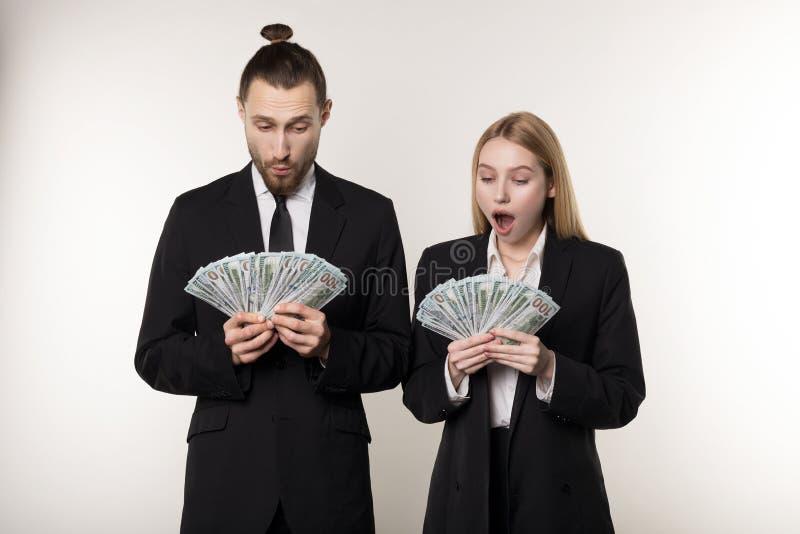Το πορτρέτο του ζεύγους στο Μαύρο ταιριάζει συγκλονισμένος κρατώντας τα τραπεζογραμμάτια χρημάτων στα χέρια στοκ εικόνα