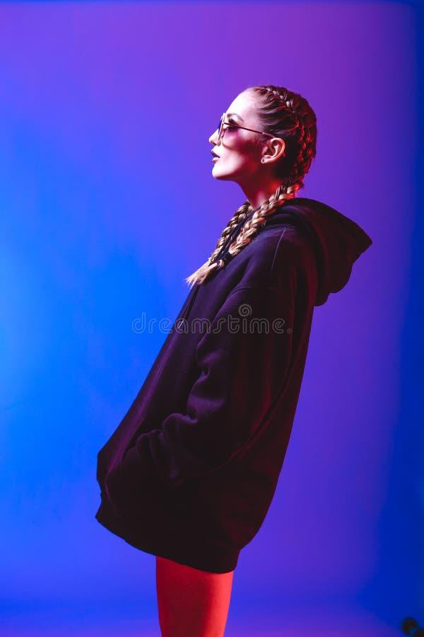 Το πορτρέτο του κοριτσιού μόδας σε ένα μαύρο πουλόβερ με μια κουκούλα και τα γυαλιά ηλίου γύρω από τη μορφή στο νέο ανάβουν στο σ στοκ φωτογραφία με δικαίωμα ελεύθερης χρήσης