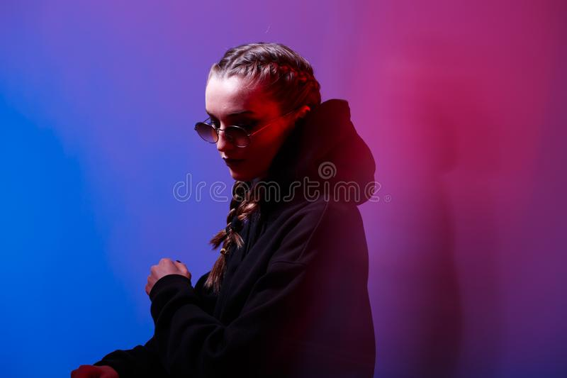 Το πορτρέτο του κοριτσιού μόδας σε ένα μαύρο πουλόβερ με μια κουκούλα και τα γυαλιά ηλίου γύρω από τη μορφή στο νέο ανάβουν στο σ στοκ εικόνες