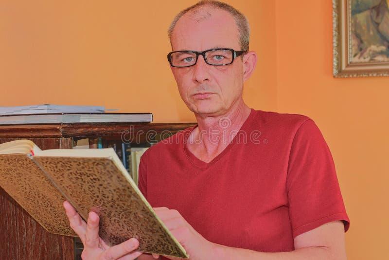 Το πορτρέτο του μέσου ηλικίας ατόμου ατόμων διαβάζει το βιβλίο στο καθιστικό Το ώριμο άτομο στέκεται δίπλα στη βιβλιοθήκη στοκ εικόνες