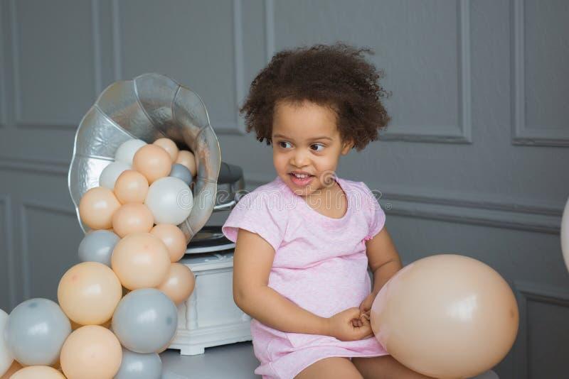 Το πορτρέτο του μαύρου μικρού κοριτσιού κάθεται, κρατά ένα μπαλόνι προσιτό και εξετάζει την πλευρά στοκ φωτογραφία με δικαίωμα ελεύθερης χρήσης