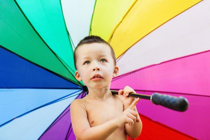 Το πορτρέτο του μικρού παιδιού με το ουράνιο τόξο χρωματίζει την ομπρέλα στοκ φωτογραφίες