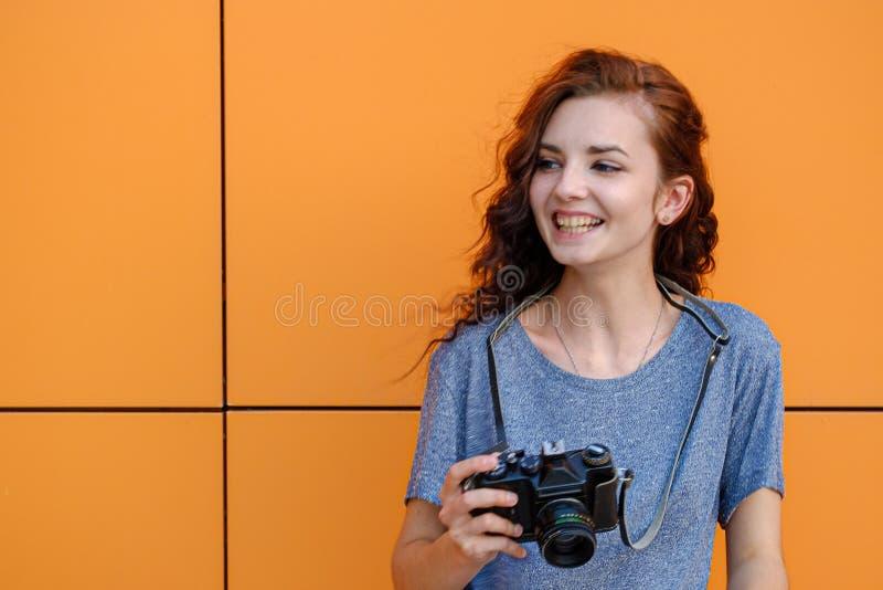 Το πορτρέτο του μοντέρνου νέου χαμόγελου φωτογράφων με την εκλεκτής ποιότητας κάμερα ταινιών σε την παραδίδει το μέτωπο του πορτο στοκ φωτογραφίες με δικαίωμα ελεύθερης χρήσης