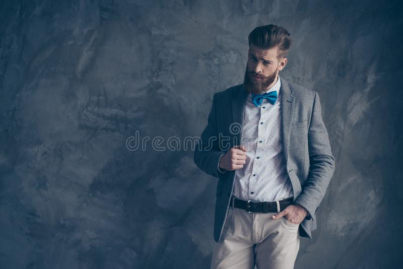 Το πορτρέτο του νέου γενειοφόρου τύπου σε ένα κοστούμι στέκεται σε ένα γκρίζο backgro στοκ φωτογραφία