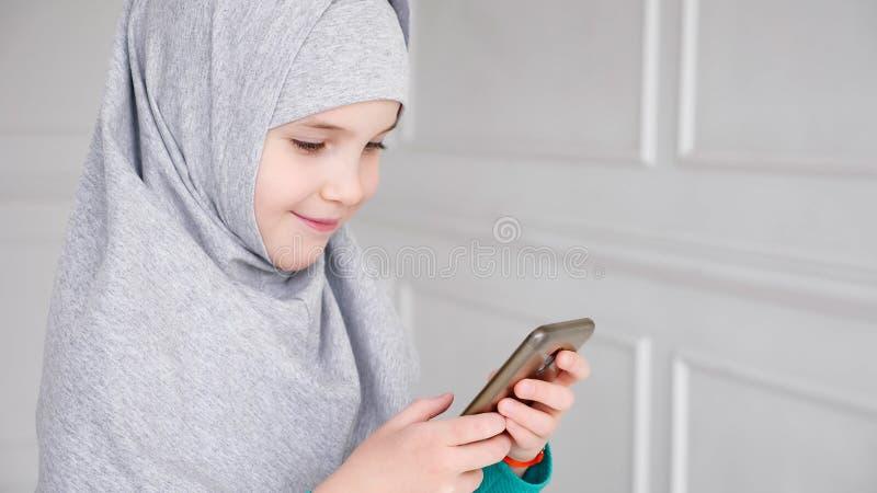 Το πορτρέτο του νέου μουσουλμανικού κοριτσιού εφήβων στο γκρίζο hijab παίζει το smartphone στοκ εικόνες