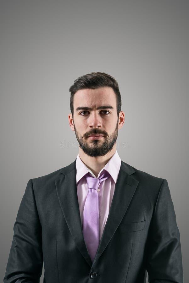 Το πορτρέτο του νέου σοβαρού επιχειρηματία με έντονο εξετάζει τη κάμερα στοκ εικόνες