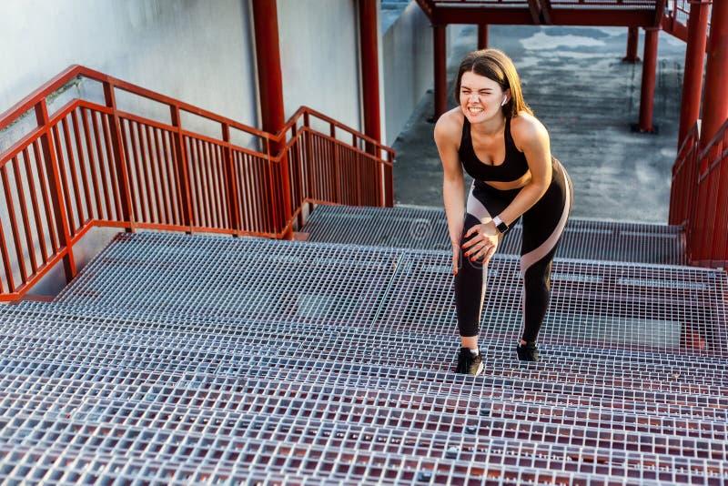 Το πορτρέτο του νέου φίλαθλου κοριτσιού στη μαύρη sportwear στάση στα σκαλοπάτια και έχει το ισχυρό βλαμμένο πρόβλημα με το γόνατ στοκ εικόνα
