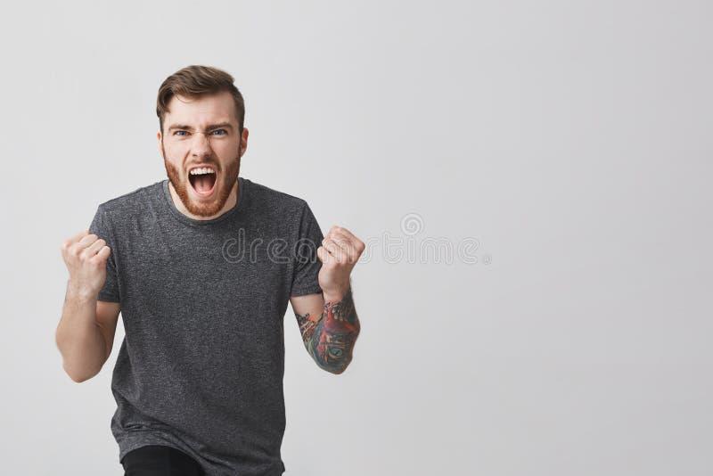 Το πορτρέτο του νέου όμορφου γενειοφόρου ευρωπαϊκού τύπου hipster με ο βραχίονας και το καθιερώνον τη μόδα κούρεμα στο περιστασια στοκ φωτογραφία