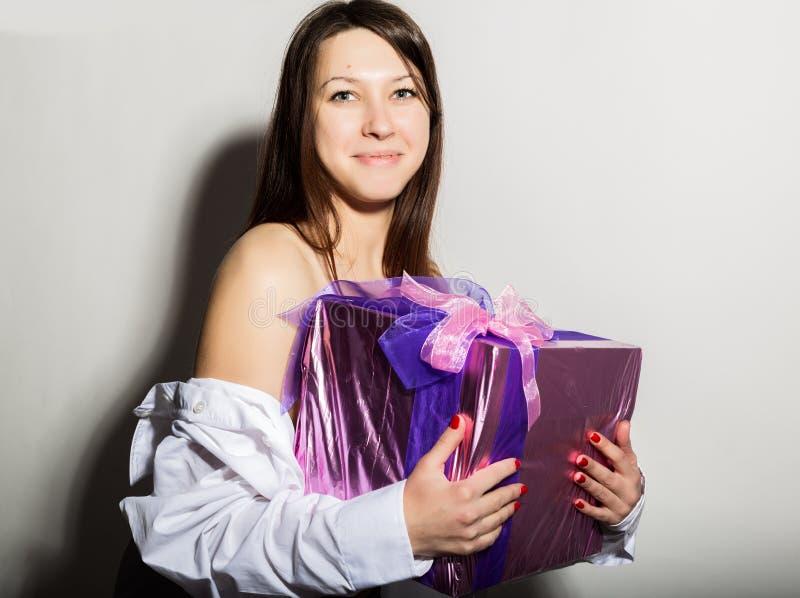 Το πορτρέτο του νέου όμορφου χαμογελώντας κοριτσιού σε ένα άσπρο πουκάμισο ατόμων ` s, που κρατά το δώρο και απολαμβάνει στοκ εικόνες
