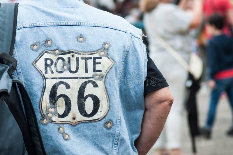 Το πορτρέτο του ποδηλάτη του Harley Dadidson με τη διαδρομή 66 φανέλλα τζιν παντελόνι στην πίσω άποψη στο αυτοκίνητο διασκέδασης  στοκ φωτογραφίες