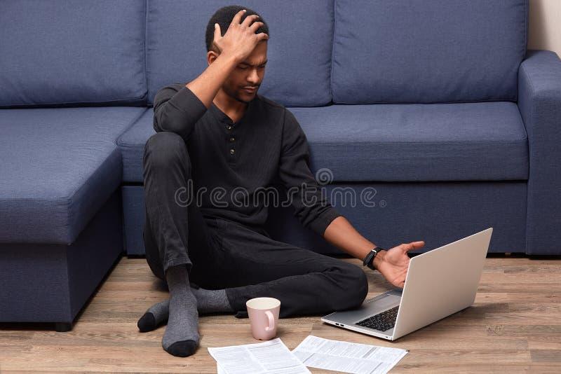 Το πορτρέτο του πολυάσχολου ανησυχημένου ατόμου σχετικά με το κεφάλι του με το χέρι, που έχει τον πονοκέφαλο, λοξοτομεί καταλαβαί στοκ φωτογραφία