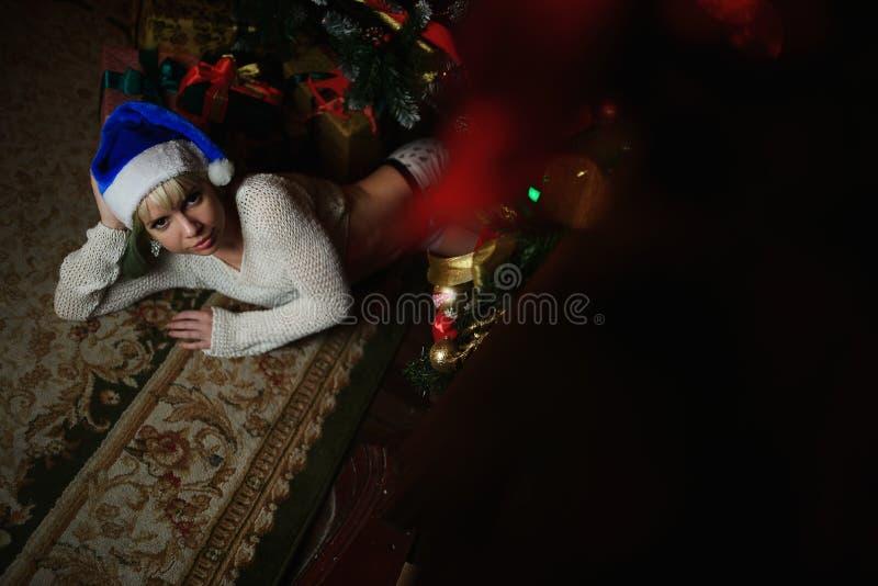 Το πορτρέτο του προκλητικού νέου κοριτσιού βρίσκεται κάτω από το χριστουγεννιάτικο δέντρο με παρουσιάζει στοκ φωτογραφίες