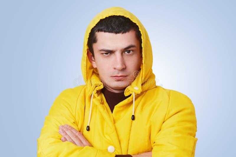 Το πορτρέτο του σοβαρού brunet τύπου hipster κρατά τα χέρια διασχισμένα, φορά το μοντέρνο κίτρινο αδιάβροχο με την κουκούλα, ακού στοκ φωτογραφίες
