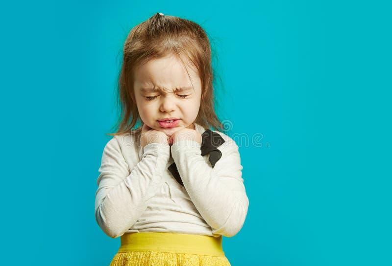 Το πορτρέτο του φοβησμένου μικρού κοριτσιού έκλεισε στενά τα μάτια στο μπλε υπόβαθρο στοκ φωτογραφία με δικαίωμα ελεύθερης χρήσης